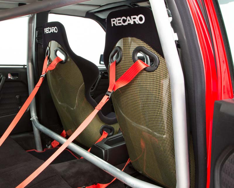 Recaro Kevlar race seats and red four-point harnesses.