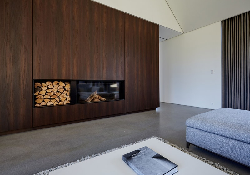 custom-designed furniture in smoked oak compliments the fireplace.
