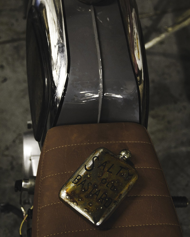 Flask on a cafe racer brown leather seat
