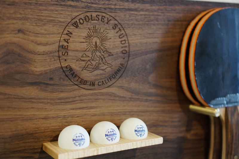 two custom-made paddles also in black walnut as well as 3-star balls and a wall-mounted rack to display the handcrafted equipment