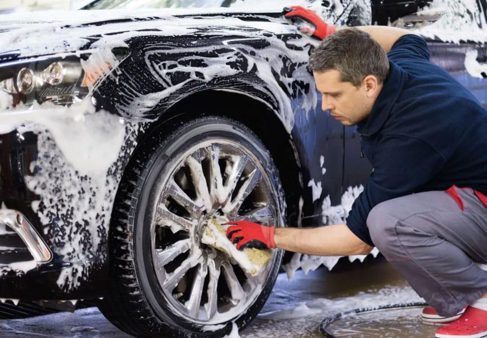 Man washing his cars alloy wheels